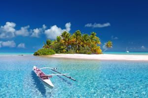 white sand island with coconut trees surrounded with clear water beach with a floating canoe