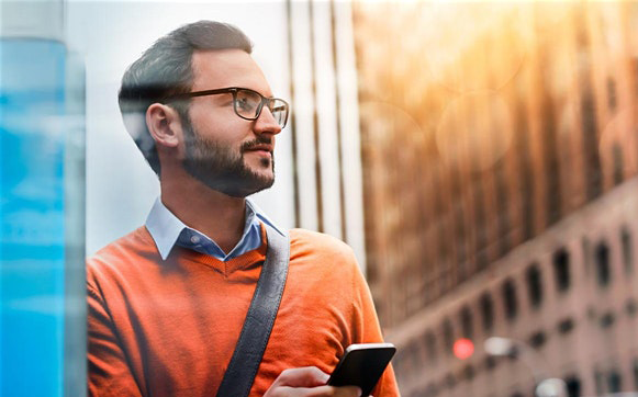guy with glasses wearing orange top holding-a phone
