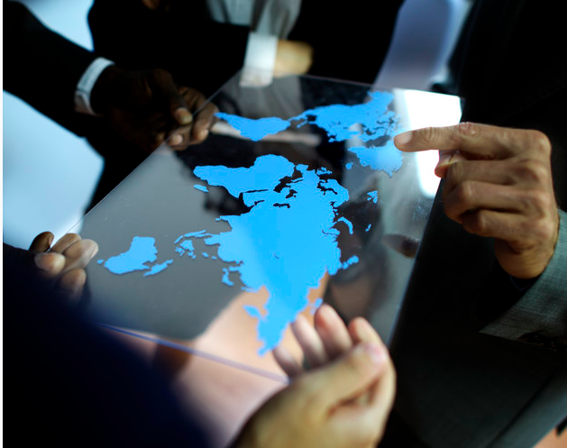people holding a glass with the world map on it